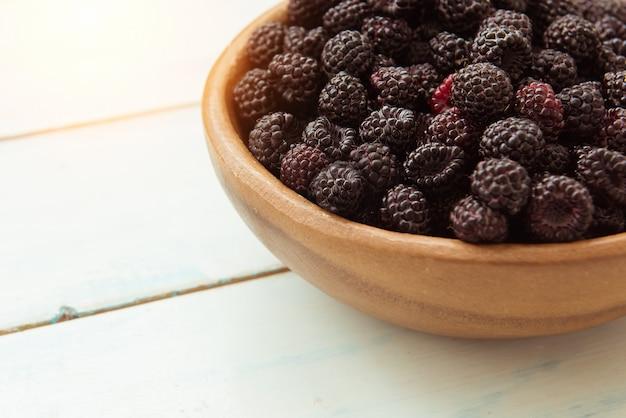テーブルの上椀で熟した新鮮なブラックベリー