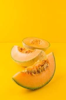 Ripe fresh cantaloupe slices on yellow background