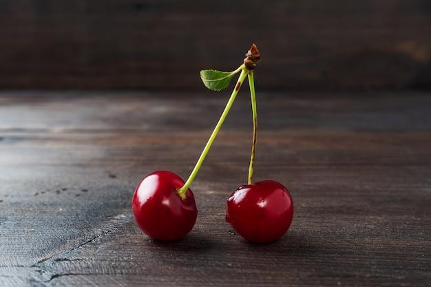 木製の素朴な背景に葉を持つ枝に熟した新鮮なチェリーベリー。