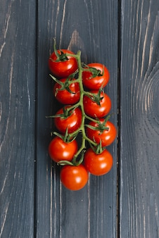 Ripe fresh cherry tomatoes on branch against black wooden plank