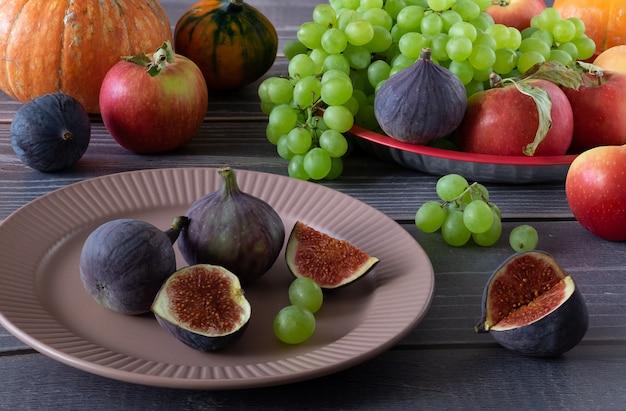 木の表面のテーブルの上に熟した新鮮なイチジク、ブドウ、リンゴ、カボチャ。