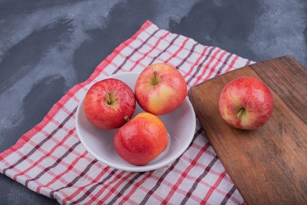 Спелые, свежие четыре яблока на белой тарелке.