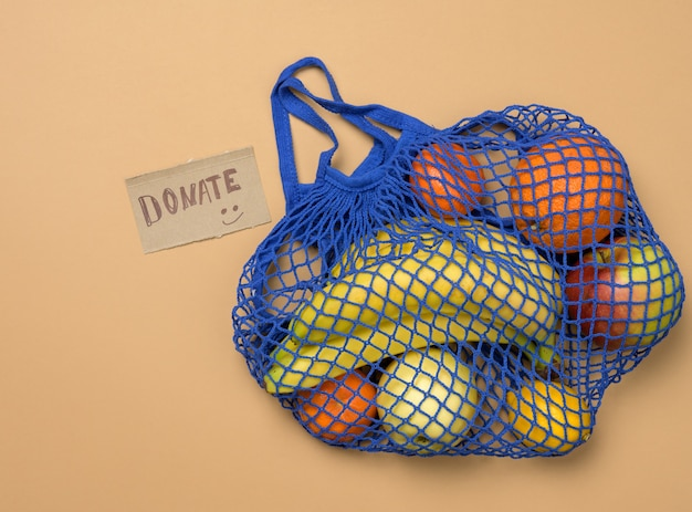 Ripe fresh fruits in a textile string bag on a brown background, top view