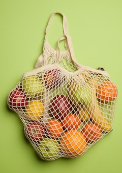 Ripe fresh fruits in a textile string bag on a green background, top view