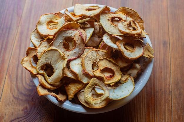 ビタミンを含む熟した新鮮な健康的な食事の菜食主義の食糧皿の上のリングの形の乾燥したリンゴ