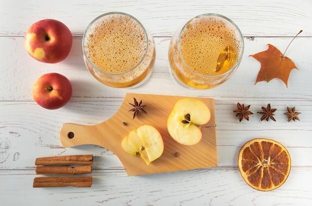 熟した新鮮なジューシーな赤いリンゴ、スパイス、グラス、軽い木の表面にサイダーを添えます。水平方向、セレクティブフォーカス、上面図。