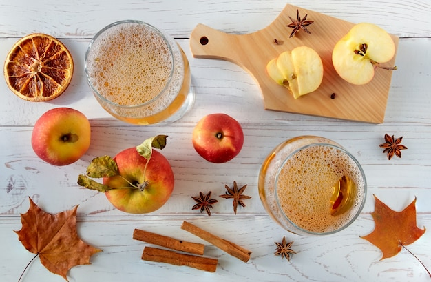 熟した新鮮なジューシーな赤いリンゴ、スパイス、グラス、軽い木の表面にサイダーを添えます。