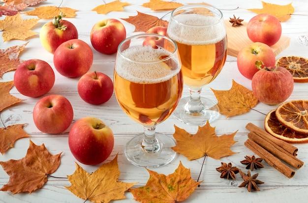 熟した新鮮なジューシーな赤いリンゴ、スパイス、秋の葉と木の表面にサイダーとグラス