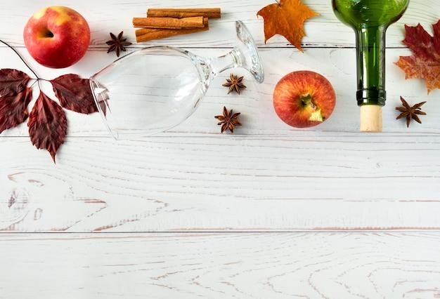 熟した新鮮なジューシーな赤いリンゴ、スパイス、ボトル、秋の葉と木の表面にサイダー用のガラス