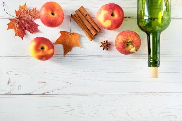 熟した新鮮なジューシーな赤いリンゴ、スパイス、秋の葉のある明るい木の表面のボトル。