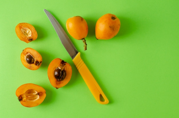 Ripe fresh loquats and nkife on green