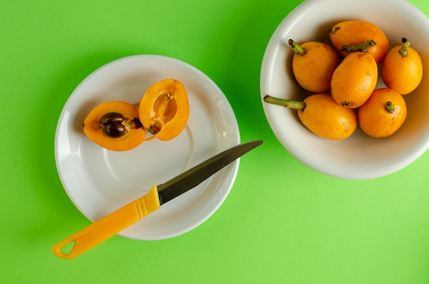 Ripe fresh loquats on white plate and nkife on green