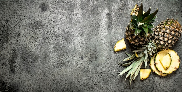 Ripe fresh pineapples on rustic table.