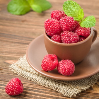 Ripe fresh raspberries with green mint leaves in brown cup and saucer on wooden background