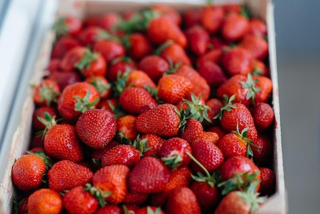 販売のためのコンテナーに熟した新鮮なイチゴのクローズアップ。健康的なダイエット。