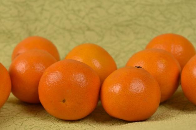 Спелые свежие мандарины на светло-зеленом фоне
