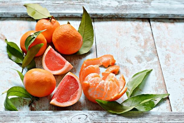 Спелые свежие мандарины с листьями на деревянном синем фоне