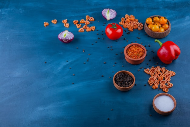 Ripe fresh vegetables and various condiments on blue surface.