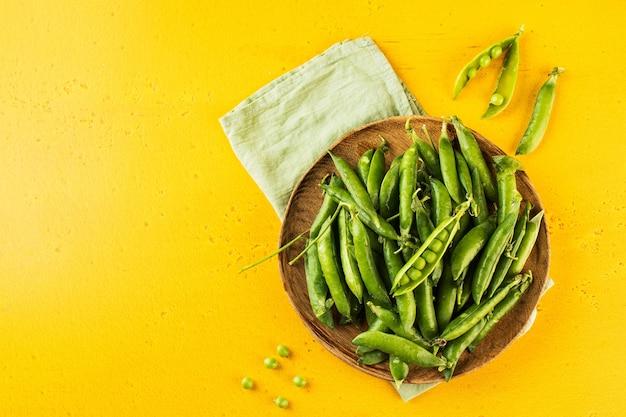 Спелый свежий молодой зеленый горошек в деревянной тарелке на желтом