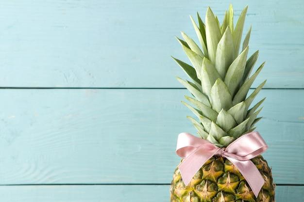 青い木製のテーブルにピンクの弓と熟したフルーツパイナップル。テキストの場所。閉じる