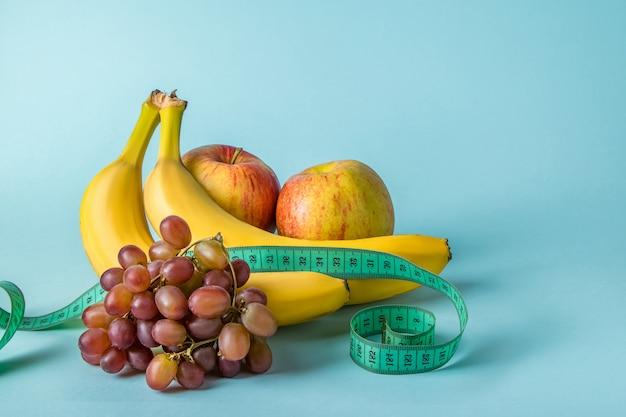 熟した果物と青い空間に巻尺。食事と適切な栄養の概念。