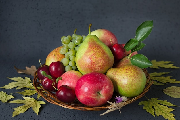 Ripe fruits in a basket, with autumn leaves.
