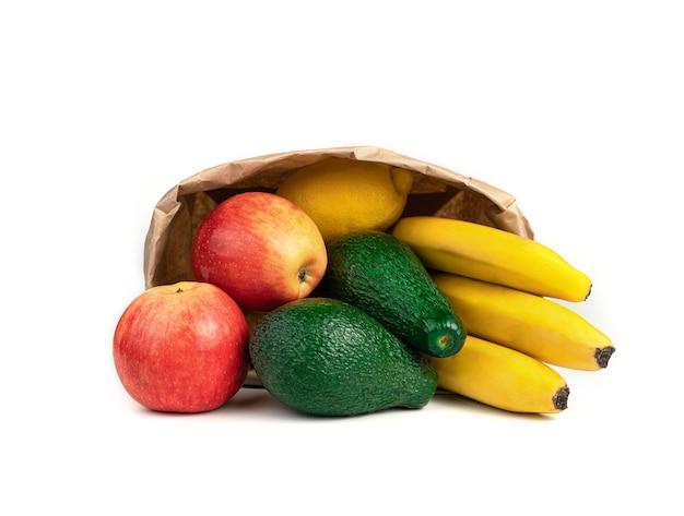 Спелые фрукты лежат на столе в крафт-сумке на белом фоне.