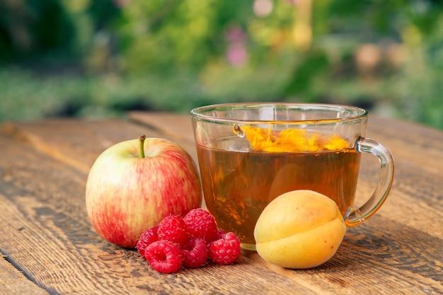 사과, 살구, 라즈베리의 익은 과일과 금송화 꽃이 든 녹차 한 잔.