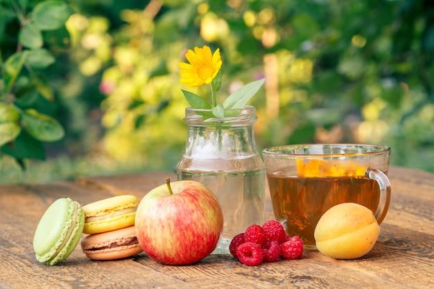 사과, 살구, 라즈베리의 익은 과일, 유리 플라스크에 줄기가 있는 금송화 꽃.