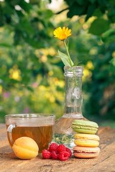 살구와 딸기의 익은 과일, 유리 플라스크에 있는 금송화 꽃, 녹차 한 잔.