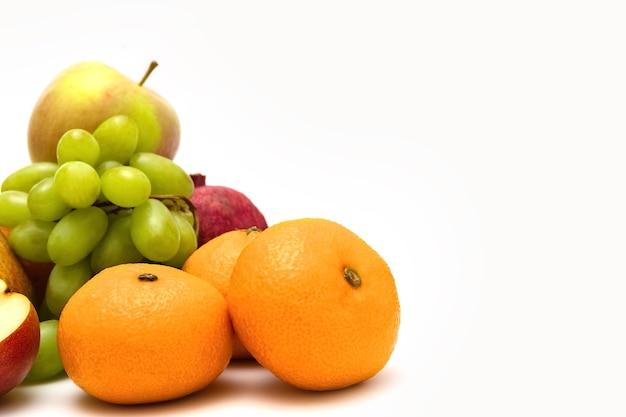 白い背景の上の熟した果物梨白い背景の上のブドウとみかんの写真
