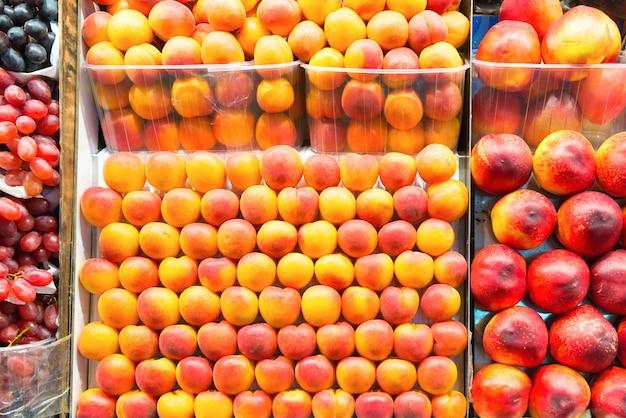 Спелые фрукты персики в коробках на фермерском рынке