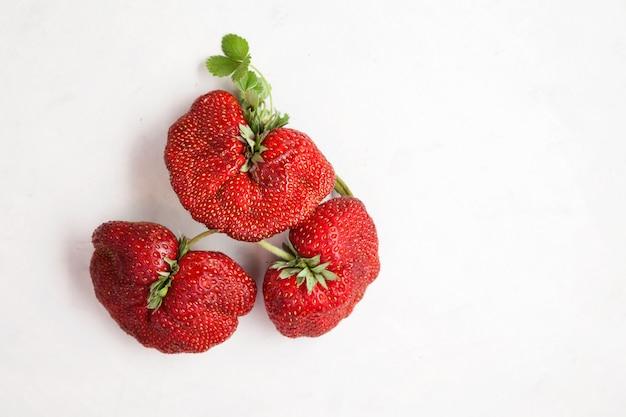 熟した面白いイチゴの果実流行の食べ物コンセプト醜い果物や野菜を食べる