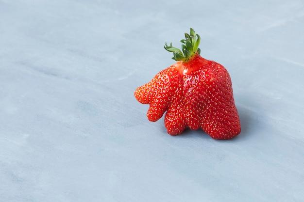 잘 익은 재미있는 딸기 베리. 트렌디 한 음식. 개념-못생긴 과일과 야채를 먹고.