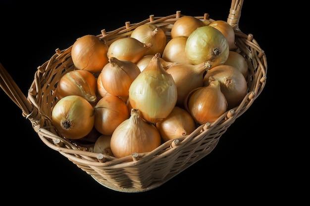 검정색 배경에 고리버들 바구니에 익은 황금 양파. 가을 선물, 수확의 계절.