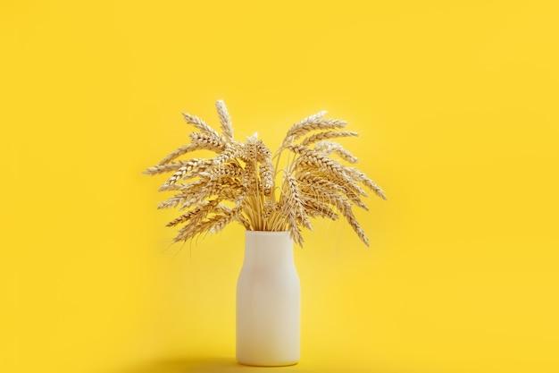 熟した金色の小麦の穂がクローズアップ白いセラミック花瓶の熟した穂の背景