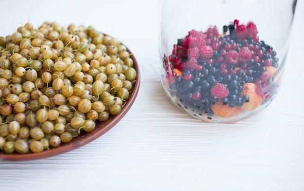 Спелый крыжовник в тарелке, летний урожай ягод