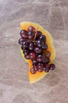 Спелый виноград на сладкой тыкве на мраморной поверхности