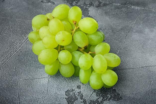 회색 돌 배경에 익은 포도 세트, 녹색 과일