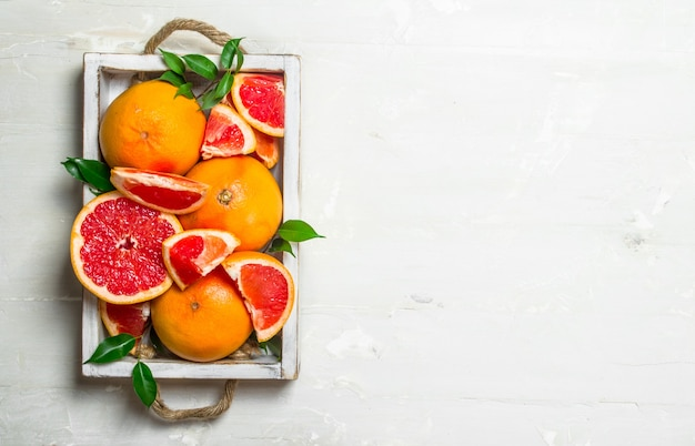 トレイに熟したグレープフルーツ。素朴な背景に