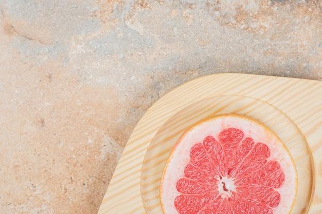 Кусочек спелого грейпфрута на деревянной тарелке. фото высокого качества