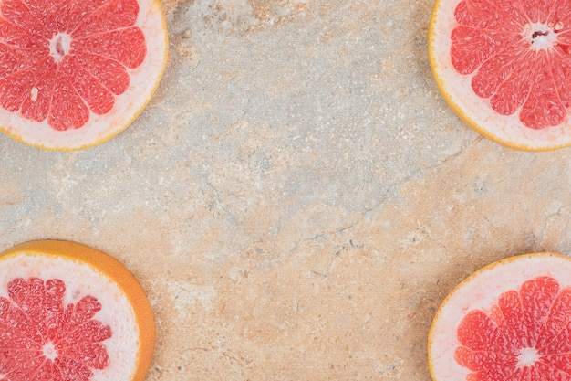 Ripe grapefruit slices on marble surface. high quality photo