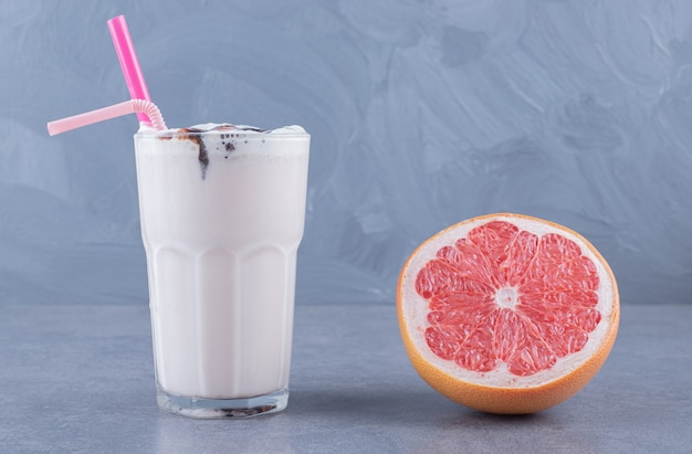 Ripe grapefruit with freshly made milk shake on table close-up.