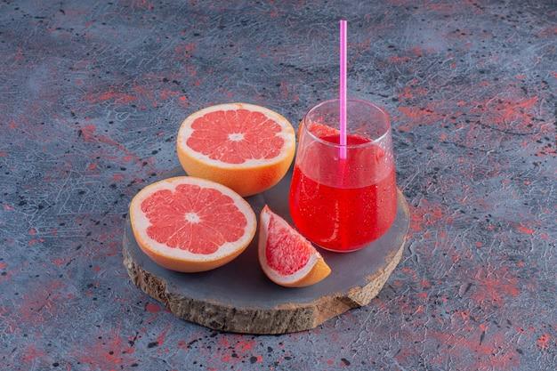 木の板にジュースと熟したグレープフルーツ