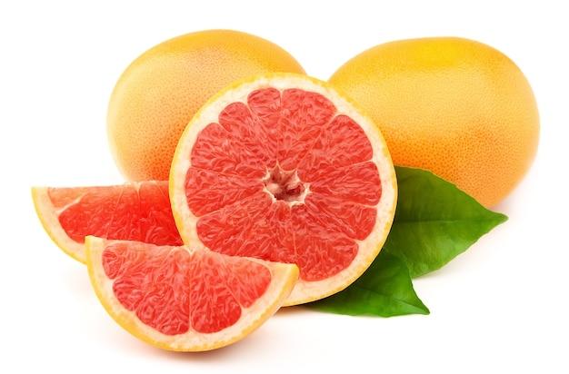 Спелый грейпфрут с листьями на белом фоне