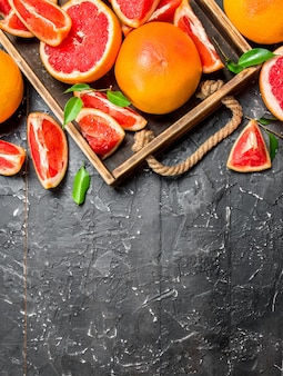 Ripe grapefruit on wooden tray on rustic table