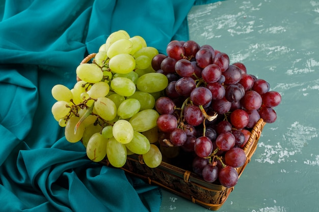 Спелый виноград в корзине на гипсе и текстиле. высокий угол обзора.