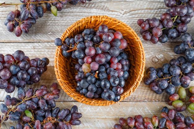 Спелый виноград в плетеной корзине на деревянном фоне. плоская планировка.