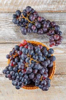 木製の背景に枝編み細工品バスケットで熟したブドウ。上面図。