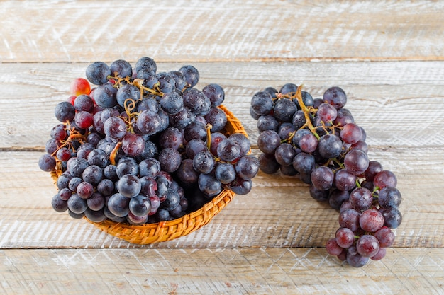 Ripe grapes in a wicker basket on wooden background, high angle view.